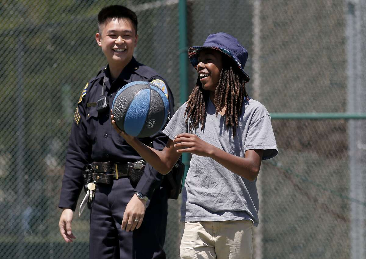 S.F. police Sgt. Ken Lee, who runs the community-based Garden Project at Garfield Park, visits with one of the project's interns, Charles Ransom.