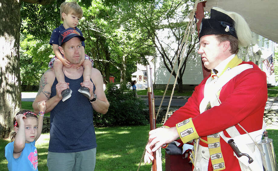 Michael Von Wahlde of Fairfield and his children, Ella, 7, and Ben, 3, listen to Colonial re-enactor Richard Young at the Fairfield Family Fun Fest on Saturday. Photo: Mike Lauterborn / Fairfield Citizen