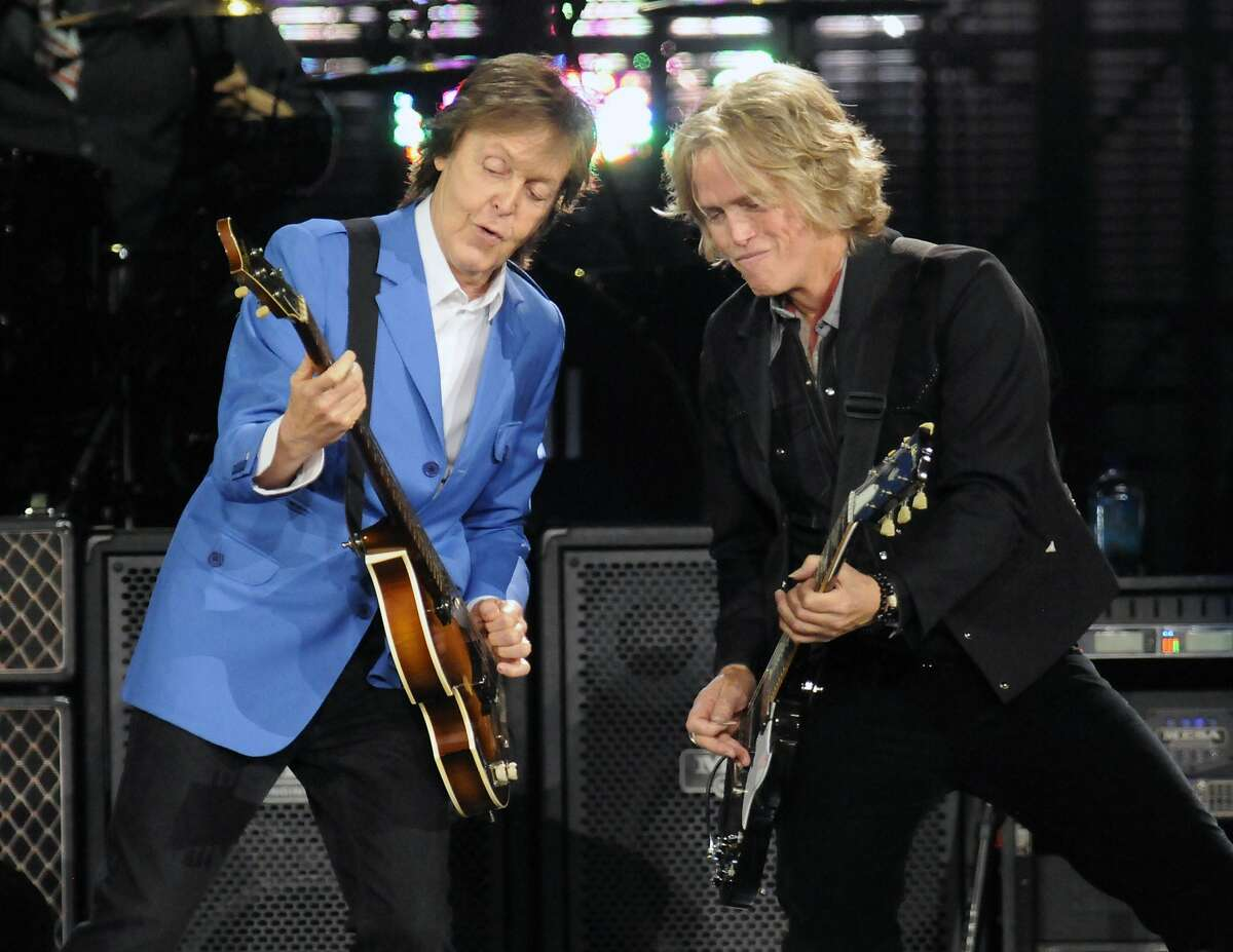 """Sir Paul McCartney, left, performs with band member Brian Ray during the """"Out There"""" Tour at the Times Union Center on Saturday, July 5, 2014, in Albany, N.Y. (Photo by Hans Pennink/Invision/AP)"""