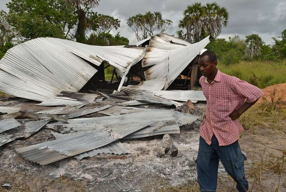 A resident of Kenya's Lamu County walks past a house that was burned down in an overnight attack. Kenyan officials blamed local separatists. Photo: Stringer, AFP/Getty Images