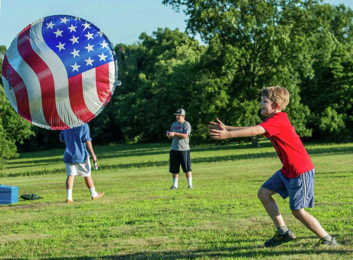 Gilbert Clay chases after an American flag hover disc at the annual Family Fourth event held at Waveny Park, New Canaan, Conn., on Saturday, July 5, 2014.