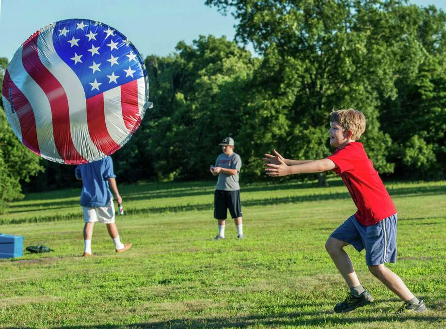 Gilbert Clay chases after an American flag hover disc at the annual Family Fourth event held at Waveny Park, New Canaan, Conn., on Saturday, July 5, 2014. Photo: Mark Conrad / Connecticut Post Freelance