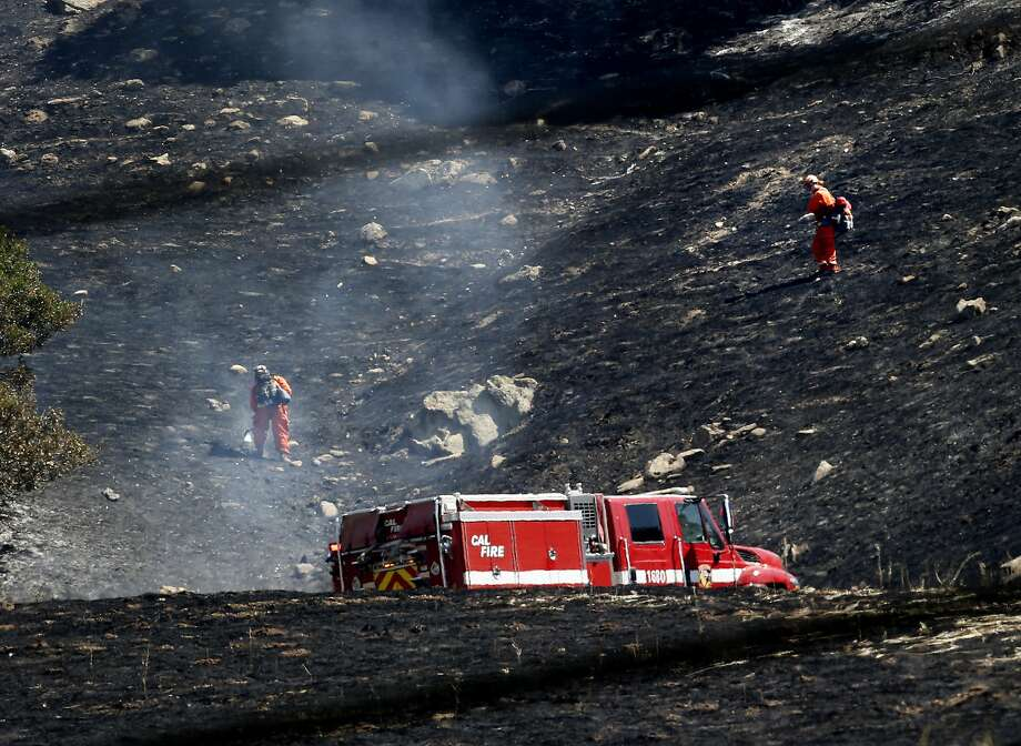 Crews worked on hot spots on the blackened hillside off highway 128. Firefighters made significant gains against the Monticello fire near Lake Berryessa Sunday July 6, 2014 and residents began returning to their homes. Photo: Brant Ward, San Francisco Chronicle