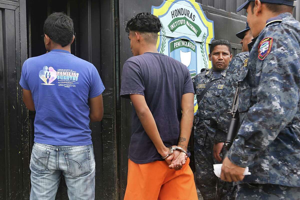 An inmate, center, is escorted into the National Penitentiary in Tegucigalpa, Honduras, as Edwin Lanza, left, a social worker with the National Prevention of Violence Program, waits to enter to meet with inmates who are gang members. Thursday, July 3, 2014.
