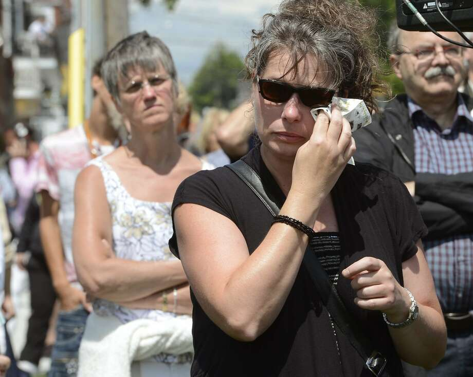 A mourner watches a service in Lac-Megantic, Quebec, on the first anniversary of a train explosion. Photo: Ryan Remiorz, Associated Press