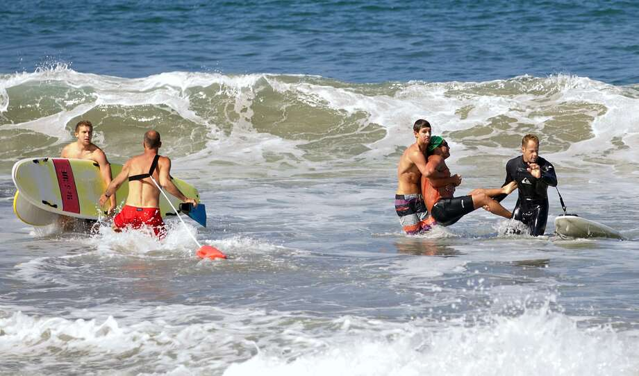 Two companions carry Steven Robles onto Manhattan Beach on Saturday after the long-distance swimmer was bitten on the chest by a great white shark. Photo: Laura Joyce, Associated Press