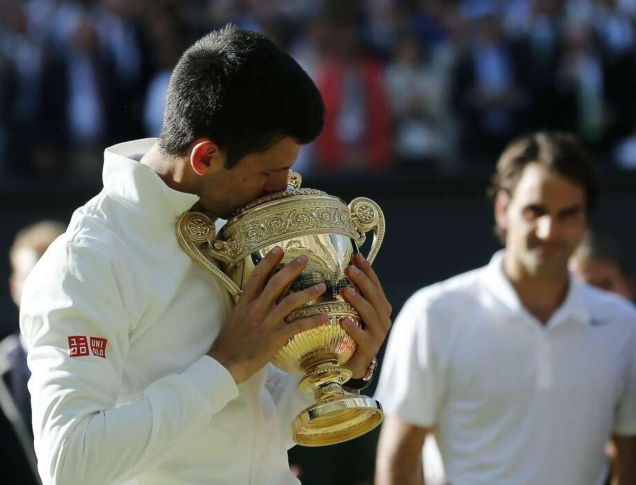 Men's singles champion Novak Djokovic kisses the Wimbledon trophy as Roger Federer watches at the All England Club. Photo: Ben Curtis, Associated Press