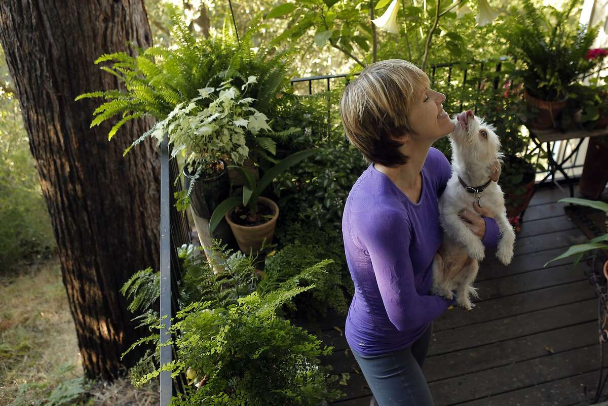 Kim Oja and her rescue dog Jack in their home in Orinda, Calif., on Wednesday, July 2, 2014. Oja says it was hard to locate housing with a dog, even in San Francisco, when she was looking for housing closer to UCSF where she is attending a nursing program. Her commute from Orinda is about 3 hours round trip using bicycle, bus and BART.
