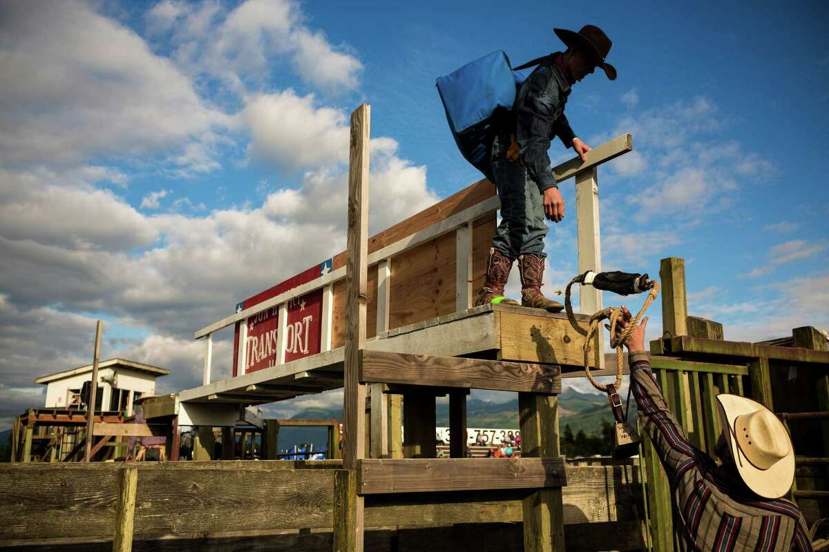 Cowboys pack into the wooden maze of stalls to prepare for the Sedro-Woolley Riding Club Rodeo Thursday, July 3, 2014, in Sedro-Woolley, Wash. The rodeo is one of many events celebrating the