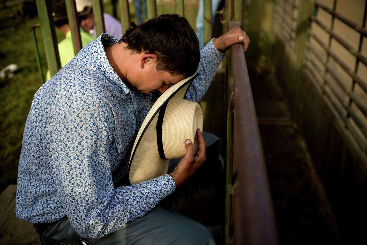 Riders take a moment to pray against the stalls before riding bucking broncos during the Sedro-Woolley Riding Club Rodeo Thursday, July 3, 2014, in Sedro-Woolley, Wash. The rodeo is one of many events celebrating the
