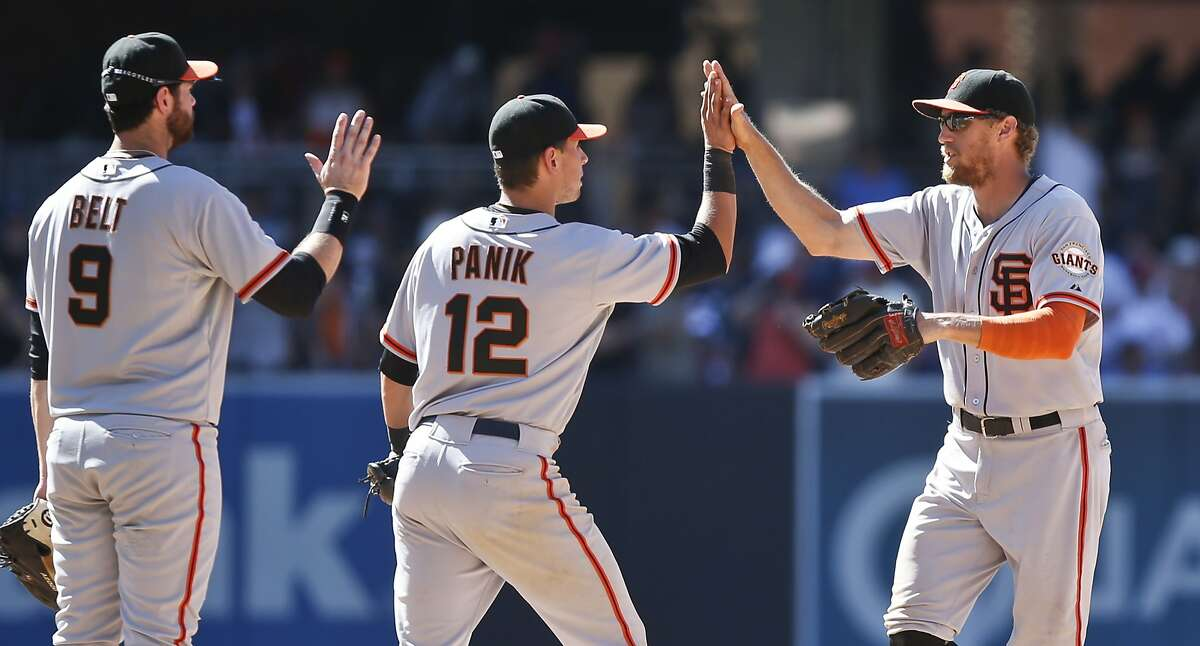 San Francisco Giants' Hunter Pence and Joe Panik high five while teammate Brandon Belt waits in line after the Giants' 5-3 victory over the San Diego Padres in a baseball game Sunday, July 6, 2014, in San Diego. Pence and Panik scored all five of the Giants' runs and Belt drove in two of the runs. (AP Photo/Lenny Ignelzi)