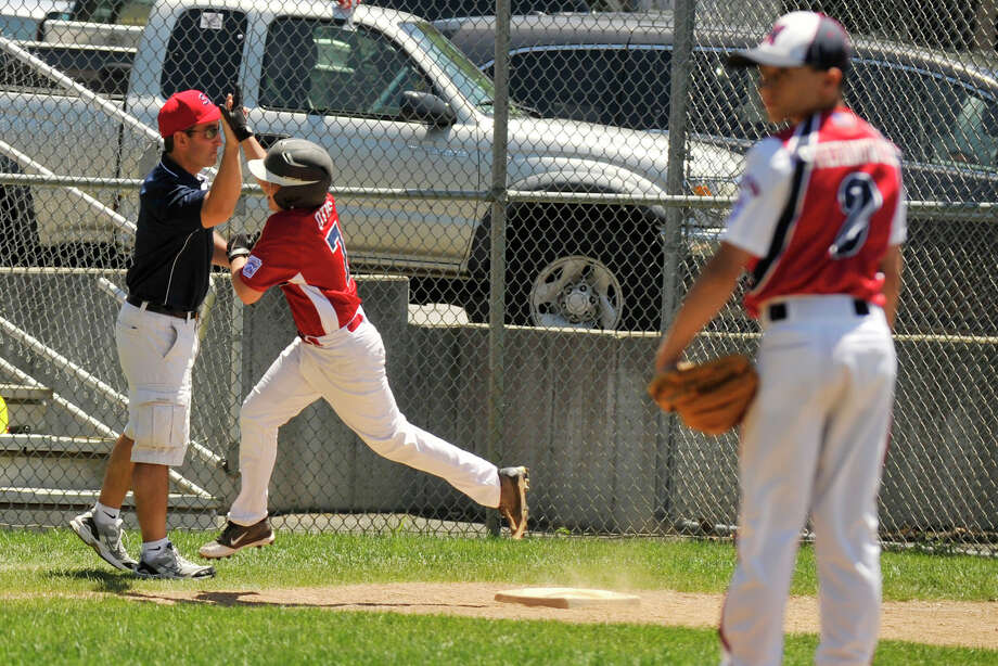 Stamford American's Nick Otis rounds third base as Norwalk starting pitcher James Stefanowicz looks on after Otis hit a home run during the American's District 1 Little League playoff game against Norwalk at Coleman Mix Field in Darien, Conn., on Sunday, July 6, 2014. Photo: Jason Rearick / Stamford Advocate