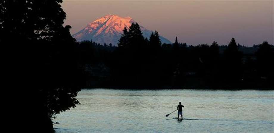 The top of Mount Rainier glows with the shades of the sunset as a paddle border goes past Pat Carey Park off Tracyton Blvd on Tuesday, July 1, 2014.(AP Photo/Kitsap Sun, Larry Steagall ) Photo: Larry Steagall, Associated Press / KITSAP SUN