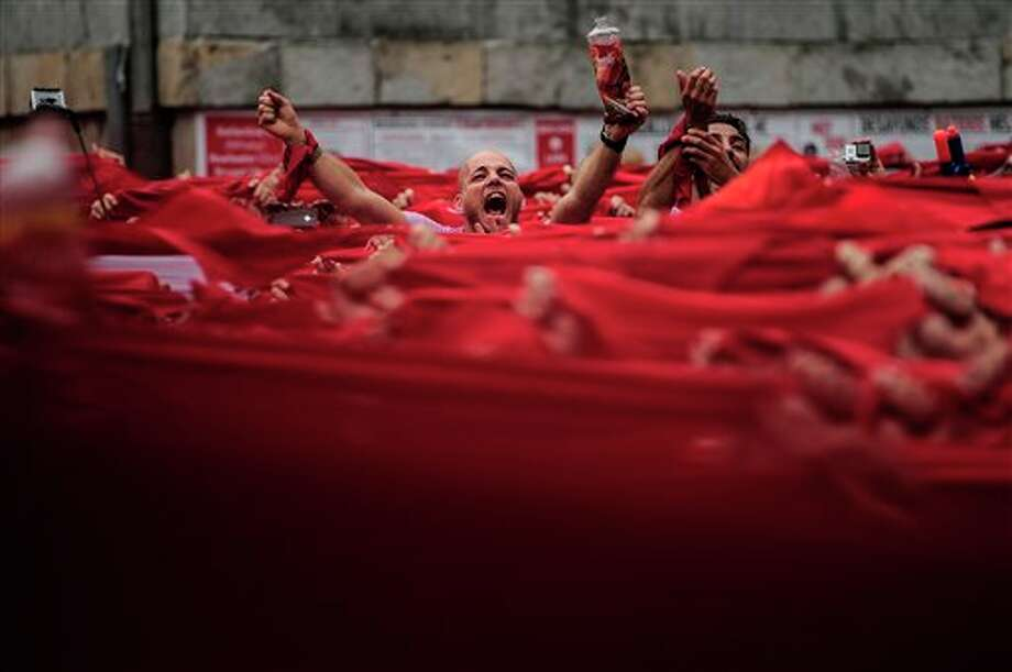 "Reveler celebrates by holding red kerchiefs, during the launch of the 'Chupinazo' rocket, to celebrate the official opening of the 2014 San Fermin fiestas, in Pamplona, Spain, Sunday, July 6, 2014. Revelers from around the world kick off the festival with a messy party in the Pamplona town square, one day before the first of eight days of the running of the bulls glorified by Ernest Hemingway's 1926 novel ""The Sun Also Rises."" (AP Photo/Alvaro Barrientos) Photo: Alvaro Barrientos, Associated Press / AP"