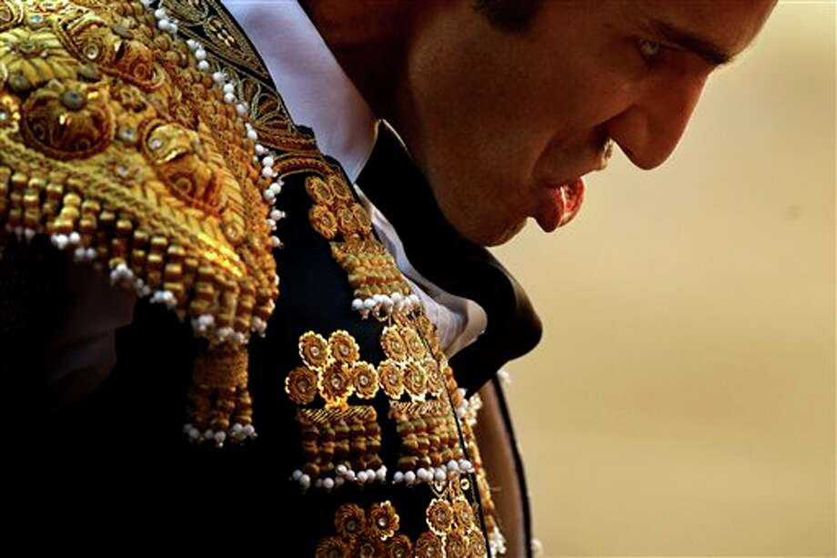 Portuguese bullfighter Manuel Dias Gomes reacts as he watches a bull die during a bullfight in Madrid, Spain, Sunday, June 29, 2014. Bullfighting is an ancient tradition in Spain. (AP Photo/Daniel Ochoa de Olza) Photo: Daniel Ochoa De Olza, Associated Press / AP