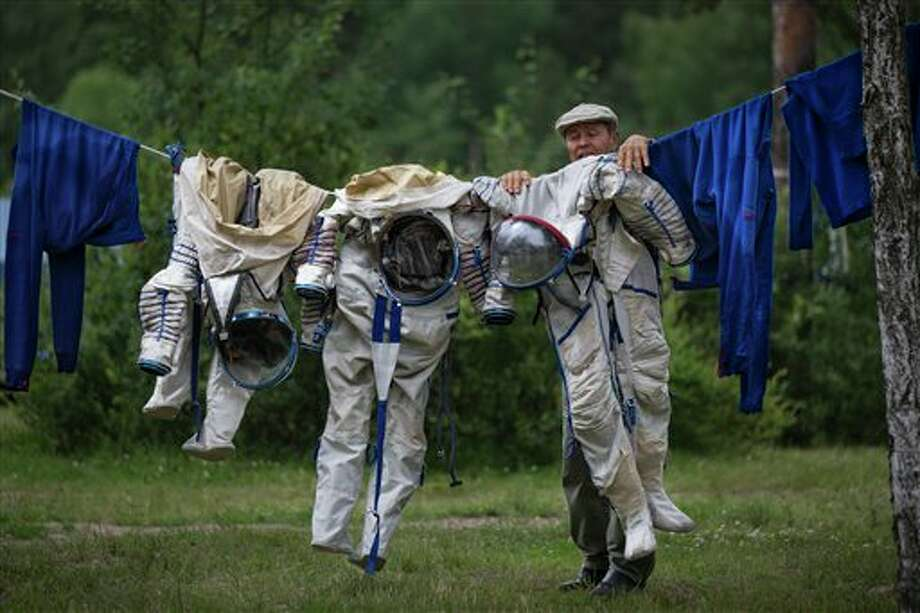 An employee of the Russian Space Training Center hangs out to dry space suits of Russian cosmonaut Anatoly Ivanishin, NASA's U.S. flight engineer Kathleen Rubins, and Japanese space agency's flight engineer Takuya Onishi, right, after their undergoing  training near in Noginsk, 60 km (38 miles) east of Moscow, Russia, Wednesday, July 2, 2014. The training was intended to simulate the capsule landing on water. Russian cosmonaut Anatoly Ivanishin, Japanese space agency's flight engineer Takuya Onishi,  and NASA's U.S. flight engineer Kathleen Rubins are being trained for a future mission to the International Space Station.(AP Photo/Alexander Zemlianichenko) Photo: Alexander Zemlianichenko, Associated Press / 2014 AP