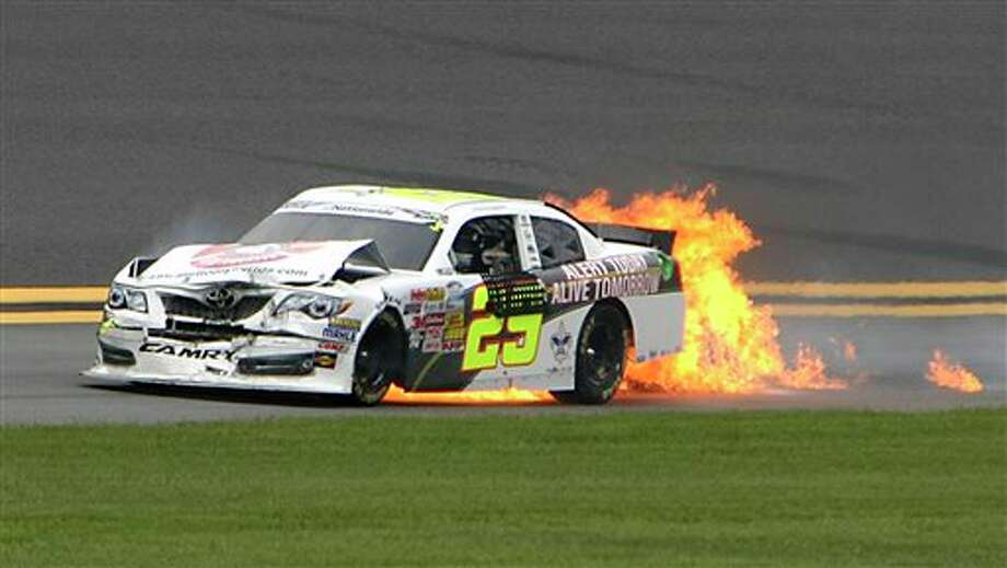 The car of driver Scott Lagasse Jr. (29) burns after he was involved in a multicar crash on the backstretch during NASCAR Nationwide series auto race qualifying at Daytona International Speedway in Daytona Beach, Fla., Friday, July 4, 2014. (AP Photo/Darryl Graham) Photo: Darryl Graham, Associated Press / FR46422 AP