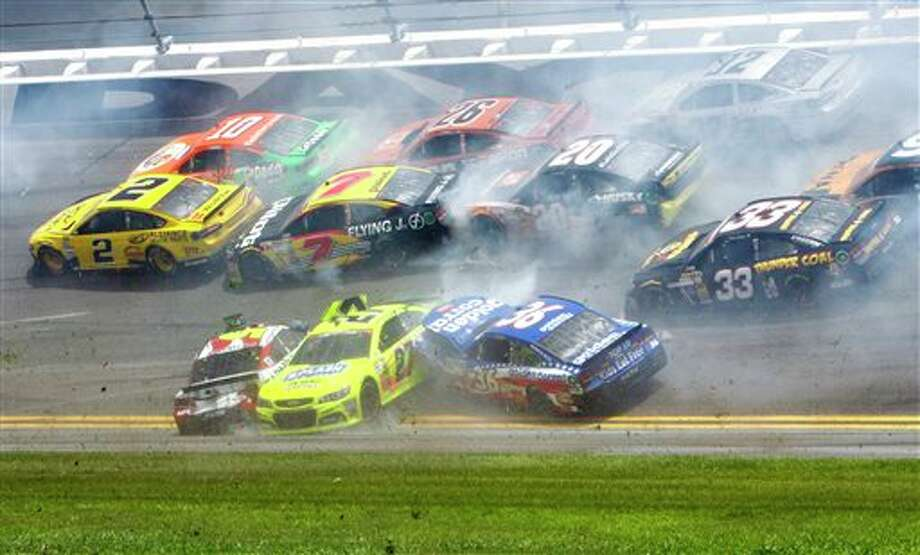 Kasey Kahne, front left, Paul Menard (27) and Reed Sorenson (36) are among the cars that crashed coming out of the backstretch going in to turn 3 during the NASCAR Sprint cup Series auto race at Daytona International Speedway in Daytona Beach, Fla., Sunday, July 6, 2014. (AP Photo/Ron Sanders) Photo: Ron Sanders, Associated Press / FR62039 AP