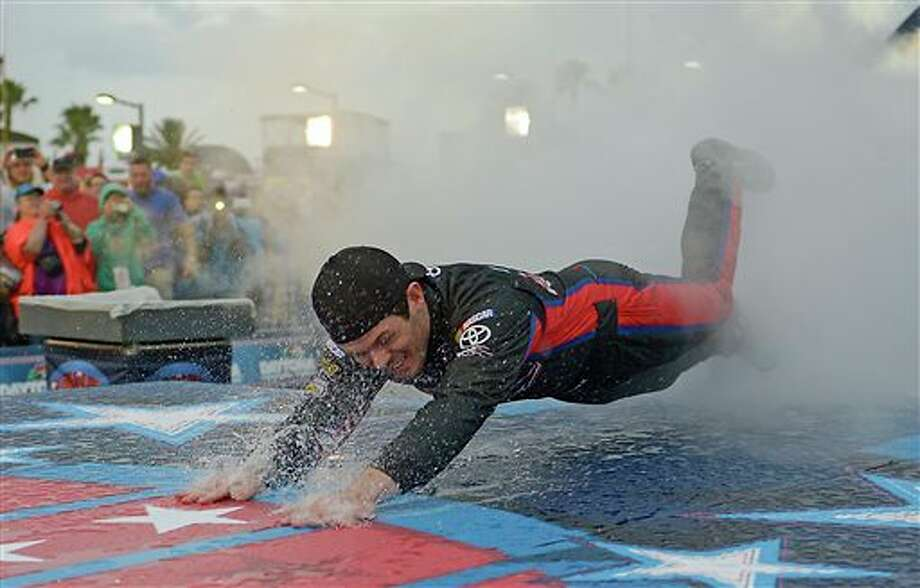 Ryan Truex dives on the rain-slick runway during introductions before the NASCAR Sprint Cup series auto race at Daytona International Speedway in Daytona Beach, Fla., Saturday, July 5, 2014. The race was later postponed until Sunday morning. (AP Photo/Phelan M. Ebenhack) Photo: Phelan M. Ebenhack, Associated Press / FR121174 AP