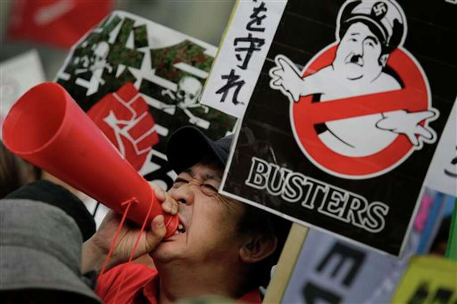 A protester shouts slogans outside the Japanese Prime Minister Shinzo Abe's office as the Cabinet approved reinterpreting the constitution on military affairs in Tokyo, Tuesday, July 1, 2014. Japan took a step away Tuesday from an American-drafted constitution that has long kept its military shackled, approving a plan to allow greater use of a force that was vanquished at the end of World War II. (AP Photo/Eugene Hoshiko) Photo: Eugene Hoshiko, Associated Press / AP