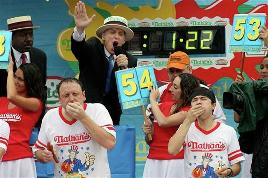 Joey Chestnut, left, and Matt Stonie, right, compete at the Nathan's Famous Fourth of July International Hot Dog Eating contest at Coney Island, Friday, July 4, 2014, in New York. Reigning champion Chestnut won his eighth contest by finishing 61 hot dogs and buns. (AP Photo/John Minchillo) Photo: John Minchillo, Associated Press / AP2014