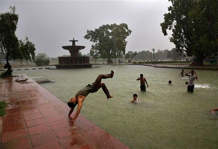 A boy somersaults into a water body as it rains in New Delhi, India, Wednesday, July 2, 2014. According to the weather office, the monsoon rains are expected to arrive at the national capital in a couple of days. (AP Photo/Manish Swarup) Photo: Manish Swarup, Associated Press / AP