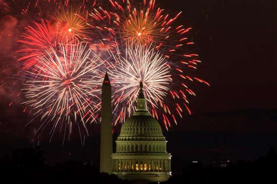 Fireworks illuminate the sky over the U.S. Capitol building and the Washington Monument during Fourth of July celebrations, on Friday, July 4, 2014, in Washington. (AP Photo/ Evan Vucci) Photo: Evan Vucci, Associated Press / AP