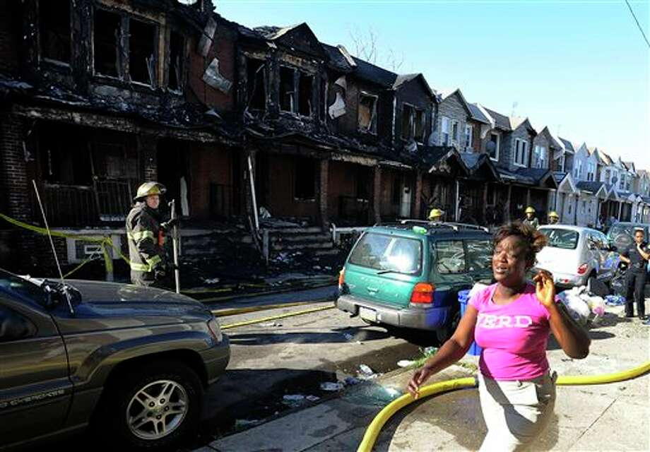 A woman cries as she walks past Philadelphia firefighters working on burned row homes on Saturday, July 5, 2014, in Philadelphia. A fast-moving fire in southwest Philadelphia early Saturday left four children dead and burned through a number of adjoining homes. (AP Photo/Michael Perez) Photo: Michael Perez, Associated Press / FR168006 AP