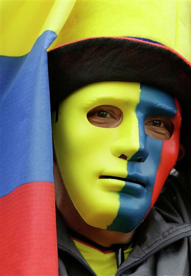 A Colombia soccer fans watches his team's World Cup quaterfinal match with Brazil on a live telecast in Bolivar square in Bogota, Colombia, Friday, July 4, 2014. (AP Photo/Fernando Vergara) Photo: Fernando Vergara, Associated Press / AP