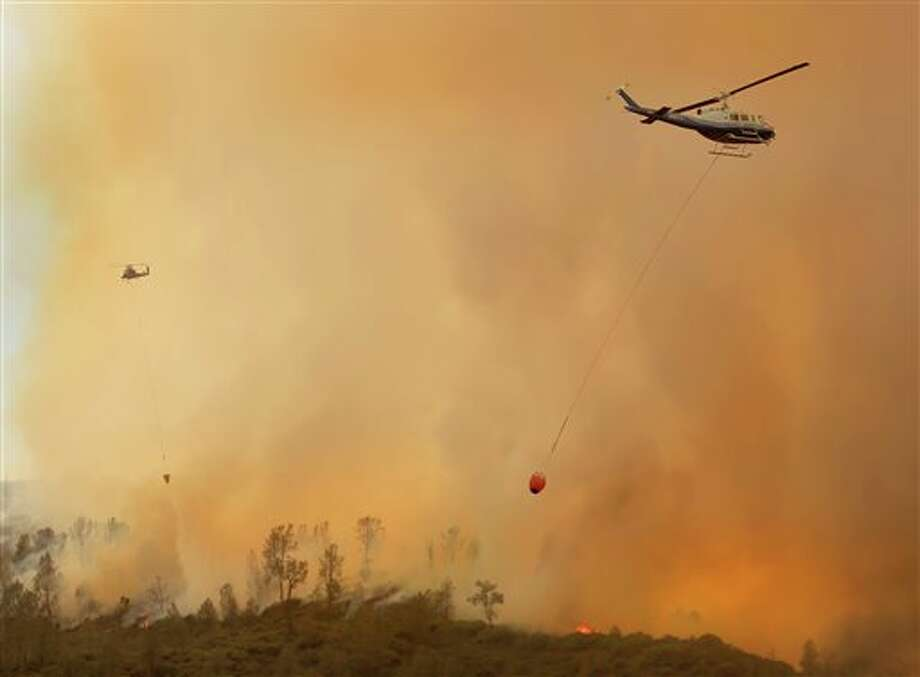 Private hire helicopters make water drops on the Butts Fire above Snell Valley as the afternoon winds kicked up, Wednesday, July 2, 2014, near Middletown, Calif. (AP Photo/Santa Rosa Press Democrat, Kent Porter) Photo: Kent Porter, Associated Press / The Press Democrat