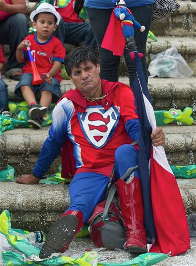 A Costa Rica soccer fan dressed as Superman rests on a set of steps after his team's World Cup loss to Netherlands after watching the quarterfinal game on a live telecast, at Democracy square in San Jose, Costa Rica, Saturday, July 5, 2014. Dutch Goalie Tim Krul came on as a substitute in the final minute of extra time and then saved two penalties in a 4-3 shootout victory over Costa Rica on Saturday, giving the Netherlands a spot in the World Cup semifinals. (AP Photo/Esteban Felix) Photo: Esteban Felix, Associated Press / AP