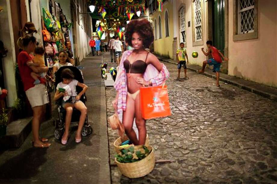 A life-size image of a woman promoting a shop stands in the street where children play soccer in the Pelourinho neighborhood of Salvador, Brazil, Monday, June 30, 2014. Salvador is one of many cities hosting World Cup soccer games. (AP Photo/Rodrigo Abd) Photo: Rodrigo Abd, Associated Press / AP