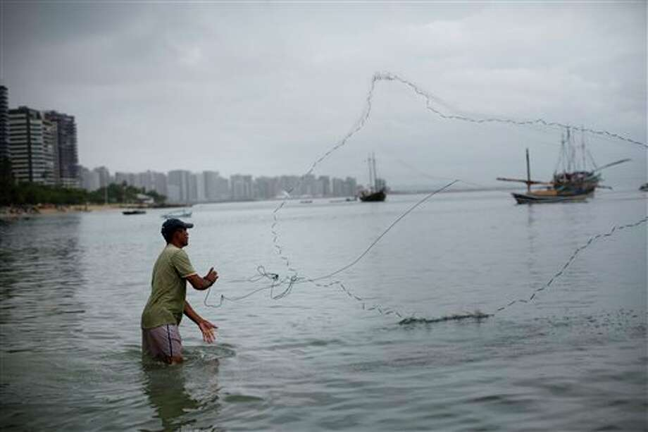 Ivan Reies casts a fishing net into the sea, along the shore of Fortaleza, Brazil, Thursday, July 3, 2014. Fortaleza is one of many cities hosting World Cup soccer matches this month. (AP Photo/Rodrigo Abd) Photo: Rodrigo Abd, Associated Press / AP