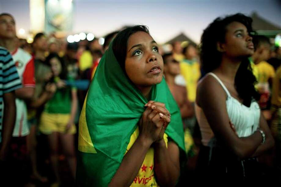 A Brazil soccer fan watches the end of a World Cup quarterfinal match between Brazil and Colombia on a live telecast inside the FIFA Fan Fest area in Taquatinga, Brazil, Friday, July 4, 2014. Brazil won 2-1 and advanced to the semifinals. (AP Photo/Rodrigo Abd) Photo: Rodrigo Abd, Associated Press / AP