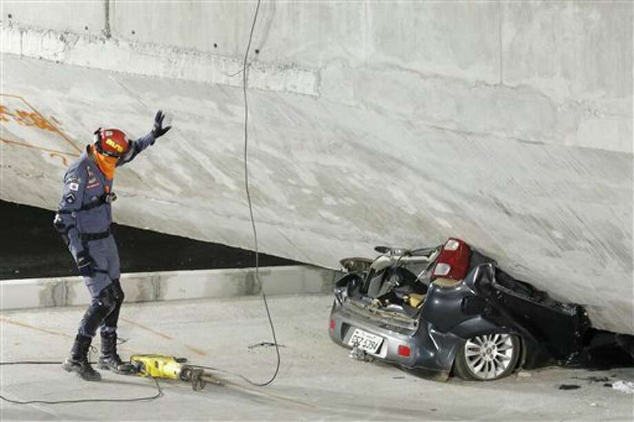 A policeman looks at a car crushed underneath a collapsed bridge in Belo Horizonte, Brazil, Thursday, July 3, 2014. The overpass under construction collapsed Thursday in the Brazilian World Cup host city. The incident took place on a main avenue, the expansion of which was part of the World Cup infrastructure plan but, like most urban mobility projects related to the Cup, was not finished on time for the event. (AP Photo/Victor R. Caivano) Photo: Victor R. Caivano, Associated Press / AP