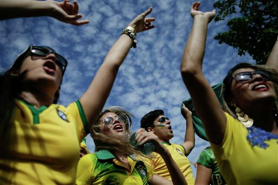 Brazilian soccer fans rev themselves up as they wait to enter the Arena Castelao, for the World Cup quarterfinal match between Brazil and Colombia, in Fortaleza, Brazil, Friday, July 4, 2014. (AP Photo/Felipe Dana) Photo: Felipe Dana, Associated Press / AP