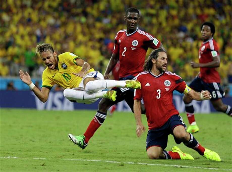Brazil's Neymar is airborne after running in to Colombia's Mario Yepes during the World Cup quarterfinal soccer match between Brazil and Colombia at the Arena Castelao in Fortaleza, Brazil, Friday, July 4, 2014. (AP Photo/Natacha Pisarenko) Photo: Natacha Pisarenko, Associated Press / AP