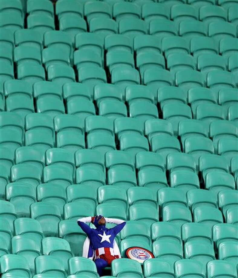 A lone USA supporter dressed as 'Captain America' sits in the stands after Belgium defeated the USA 2-1 in extra time to advance to the quarterfinals during the World Cup round of 16 soccer match between Belgium and the USA at the Arena Fonte Nova in Salvador, Brazil, Tuesday, July 1, 2014. (AP Photo/Natacha Pisarenko) Photo: Natacha Pisarenko, Associated Press / AP2014