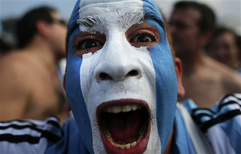 An Argentine soccer fan, his face painted to represent his team's colors, poses for a photo before the live telecast of the World Cup round of 16 match between Argentina and Switzerland, at the FIFA Fan Fest area on Copacabana beach in Rio de Janeiro, Brazil, Tuesday, July 1, 2014. (AP Photo/Leo Correa) Photo: Leo Correa, Associated Press / AP2014
