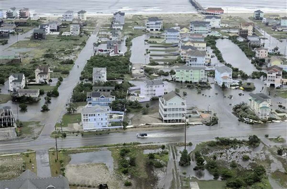 This Friday, July 4, 2014 aerial photo provided by the U.S. Coast Guard shows flooding caused by Hurricane Arthur on the Outer Banks of North Carolina. Arthur struck North Carolina as a Category 2 storm with winds of 100 mph late Thursday, taking about five hours to move across the far eastern part of the state. (AP Photo/U.S. Coast Guard, Petty Officer 3rd Class David Weydert)