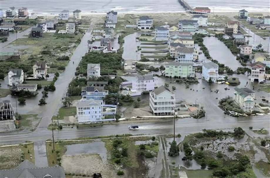 This Friday, July 4, 2014 aerial photo provided by the U.S. Coast Guard shows flooding caused by Hurricane Arthur on the Outer Banks of North Carolina. Arthur struck North Carolina as a Category 2 storm with winds of 100 mph late Thursday, taking about five hours to move across the far eastern part of the state. (AP Photo/U.S. Coast Guard, Petty Officer 3rd Class David Weydert) Photo: David Weydert, Associated Press / U.S. Coast Guard