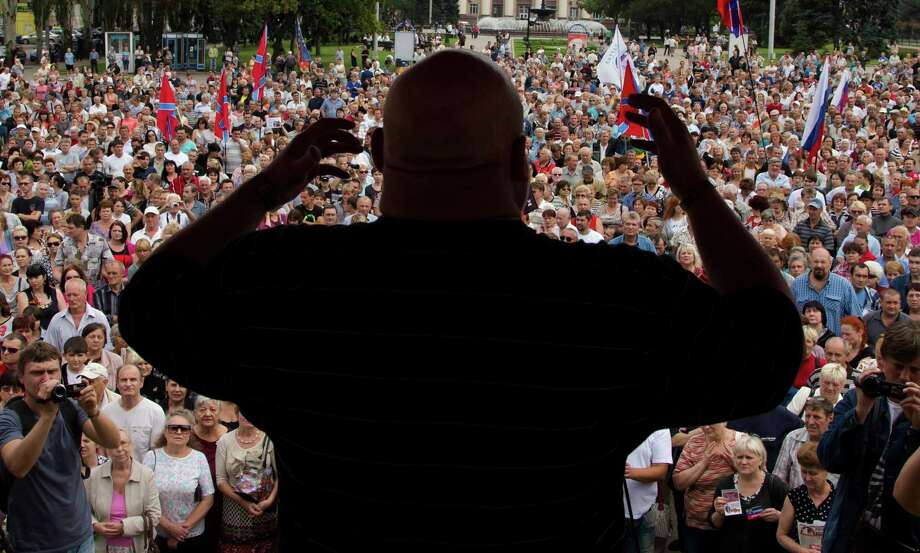 People listen to a pro-Russian activist during a pro-Russian meeting in the city of Donetsk, eastern Ukraine Sunday, July 6, 2014. More than a thousand people rallied on Donetsk's central Lenin square on Sunday afternoon in support of the pro-Russian rebellion after an important defeat yesterday. (AP Photo/Dmitry Lovetsky) Photo: Dmitry Lovetsky, STF / AP