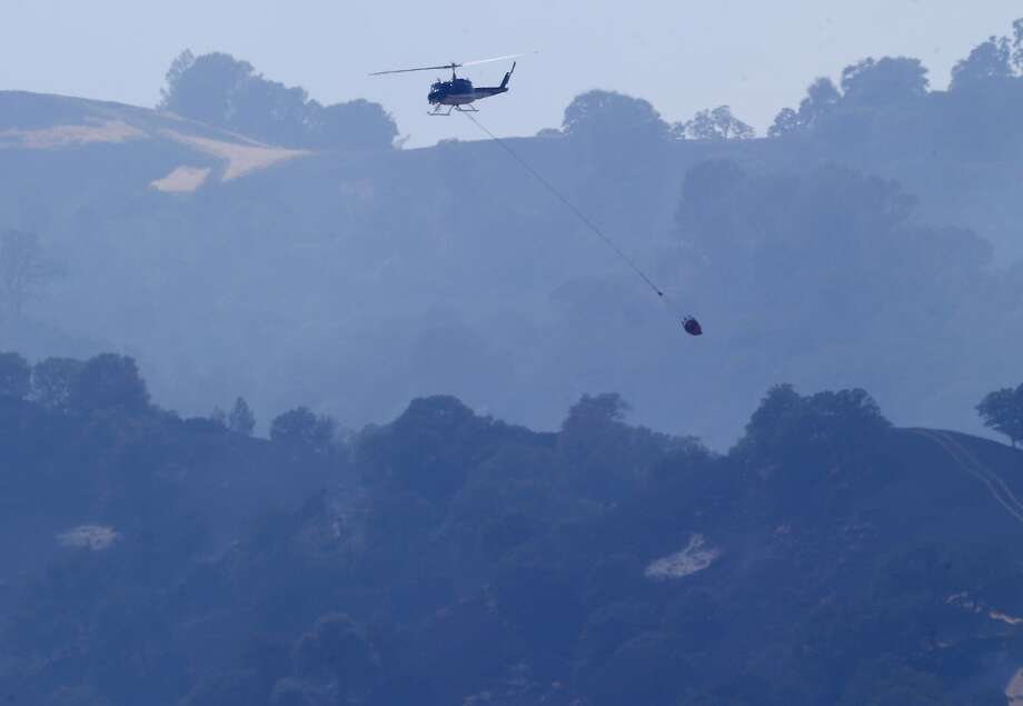 A helicopter drops water over the Monticello Fire near Lake Berryessa. Sixteen helicopters and six planes were used to battle the blaze that broke out Friday. Photo: Brant Ward, San Francisco Chronicle