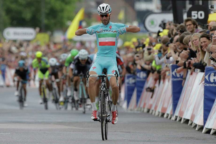 Italy's Vincenzo Nibali points to his shirt as he crosses the finish line ahead of the sprinting pack to win the second stage of the Tour de France cycling race over 201 kilometers (124.9 miles) with start in York and finish in Sheffield, England, Sunday, July 6, 2014. (AP Photo/Laurent Cipriani) ORG XMIT: PDJ111 Photo: Laurent Cipriani / AP