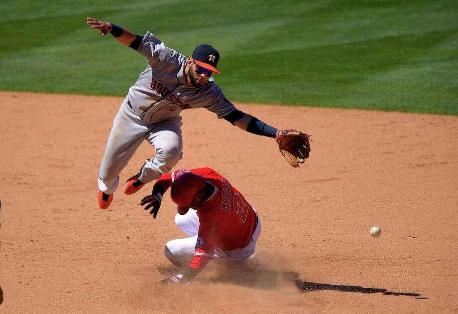 Astros shortstop Marwin Gonzalez, top, misses an errant throw from catcher Carlos Corporan on a steal by Erick Aybar, with the error allowing one run to score and setting up another run. Photo: Mark J. Terrill, STF / AP