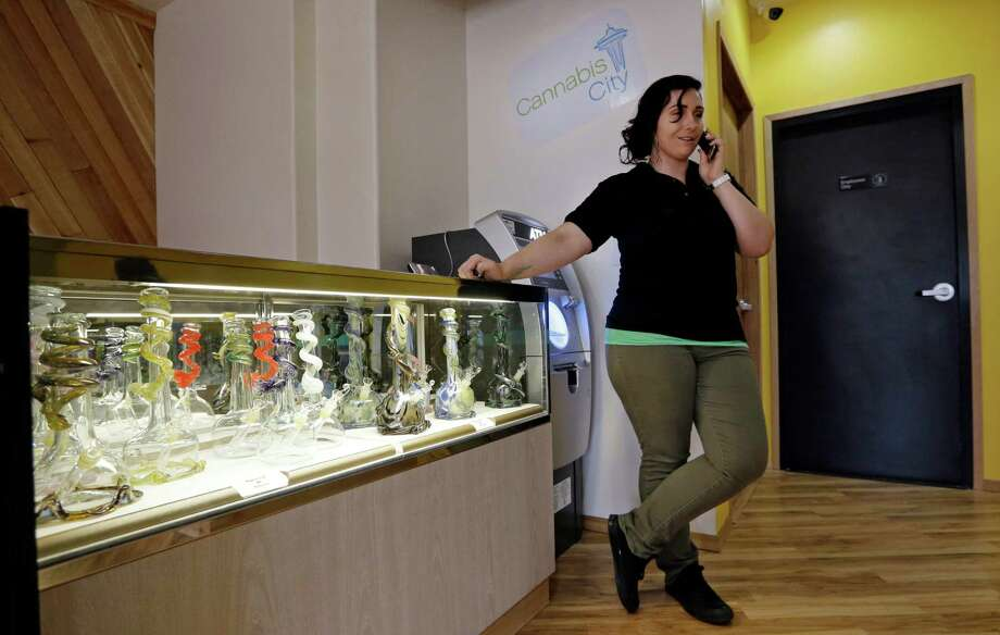 Cannabis City manager Amber McGowan takes the marijuana shop's first call, from a potential customer, days before the grand opening Wednesday, July 2, 2014, in Seattle. The store expects to begin selling pot Tuesday, July 8, the first day that recreational marijuana can legally be sold in Washington state and is expected to be the first licensed retailer in Seattle. (AP Photo/Elaine Thompson) Photo: Elaine Thompson, STF / AP