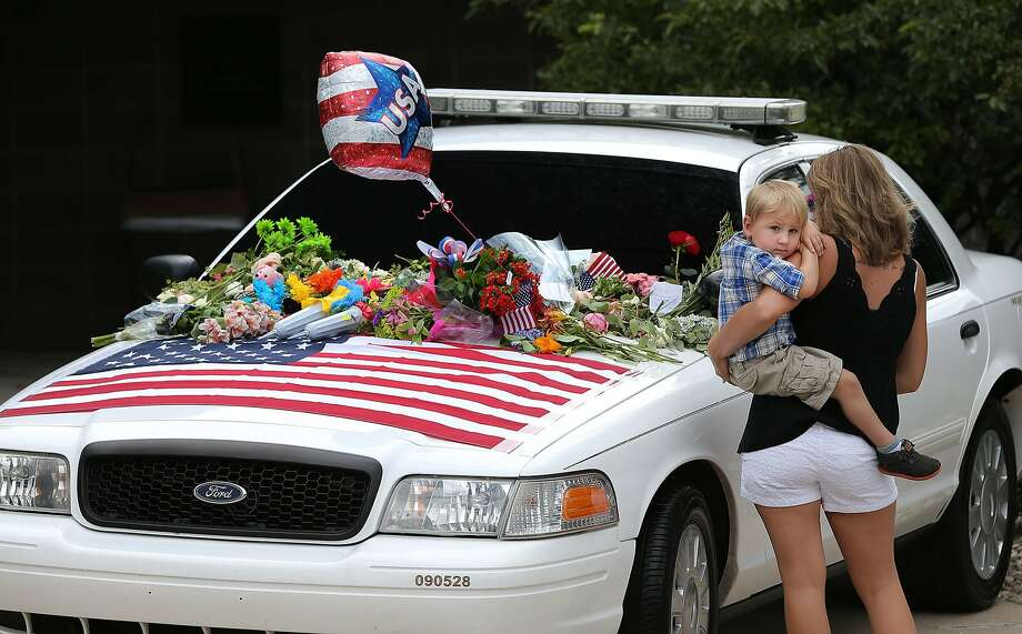 A memorial set up for Indianapolis Metropolitan Police Department Officer Perry Renn is seen at the north district police headquarters in the Washington Park section of Indianapolis on Sunday, July 6, 2014. Renn, 51, died after he and another patrolman exchanged gunfire with a suspect in an alley Saturday, July 5. He had been with the IMPD for nearly 22 years. (AP Photo/The Indianapolis Star, Matt Kryger) Photo: Matt Kryger, Associated Press