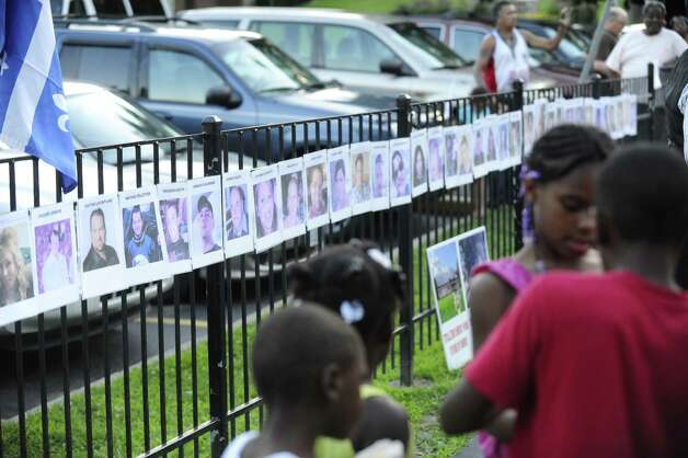 Photographs of those killed in the Lac Megantic oil train disaster are seen on a fence during a vigil at the Ezra Prentice Homes on Sunday, July 6, 2014, in Albany, N.Y., to remember the Lac Megantic oil train disaster that occurred a year ago in which 47 people died when a runaway train derailed and exploded. (Paul Buckowski / Times Union)