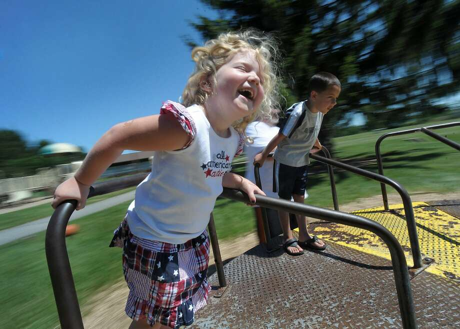 Isabella Mendez, left, 3, of Macungie, and her cousin C.J. Stumpf, right, 5, of East Allen Township, are spun on a merry-go-round as they take advantage of great weather to close out the holiday weekend Sunday July 6, 2014,  at Hanover Township Municipal Park, Pa . (AP Photo/The Express-Times, Matt Smith) Photo: Associated Press