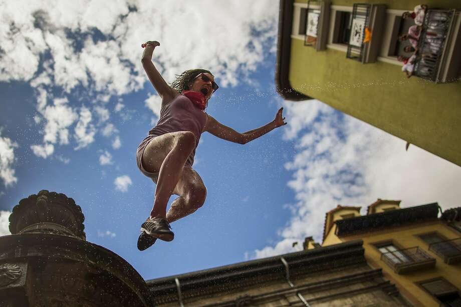 "A reveler jumps from a fountain onto the crowd below, after the launch of the 'Chupinazo' rocket, to celebrate the official opening of the 2014 San Fermin fiestas in Pamplona, Spain, Sunday, July 6, 2014. Revelers from around the world turned out here to kick off the festival with a messy party in the Pamplona town square, one day before the first of eight days of the running of the bulls glorified by Ernest Hemingway's 1926 novel ""The Sun Also Rises."" (AP Photo/Andres Kudacki) Photo: Andres Kudacki, Associated Press"